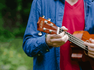 small image of man playing ukulele left handed