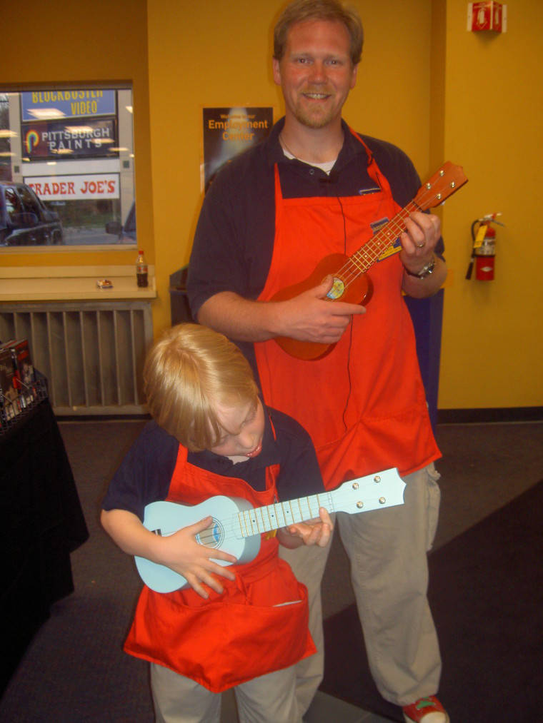 a father and son playing ukulele